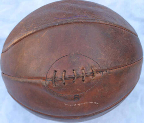 Rugby ball circa 1900. Quite round but slightly elongated. Pigs bladder wrapped in leather. Dark Tan colour